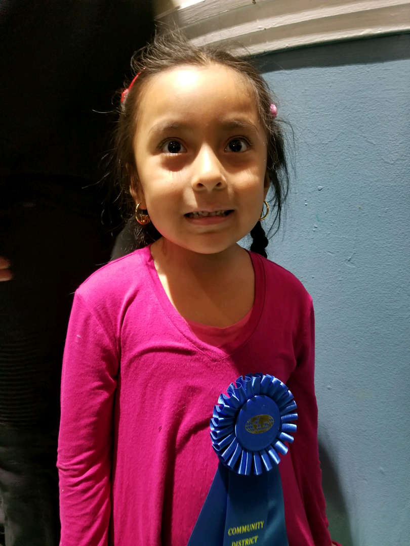 our youngest student poses with blue ribbon for her participation in history fair