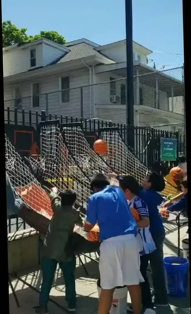 children practice shooting basketballs through hoops