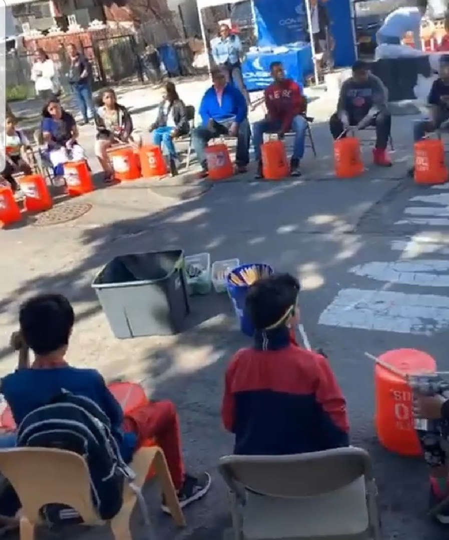 students beating plastic buckets as drums in street