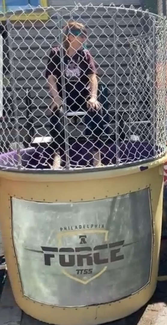 students prepare to dunk teacher in water by hitting target