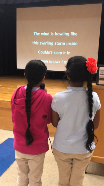students follow words on screen as they do karaoke