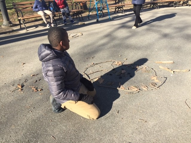 student works on art forms in park
