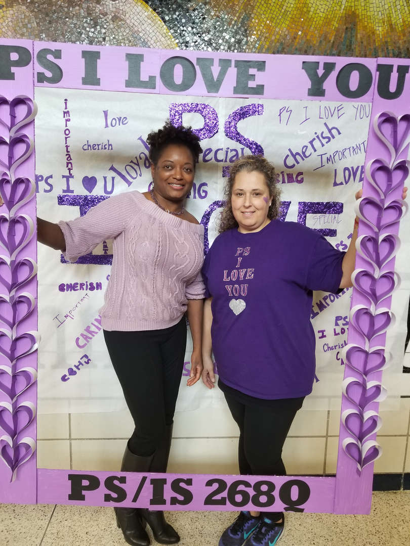 Principal and  Guidance counselor pose in purple picture frame to celebrate ps i love you day