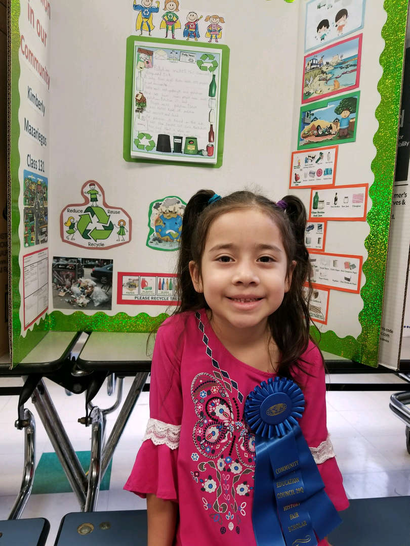 young girl smiles as blue ribbon winner for history project