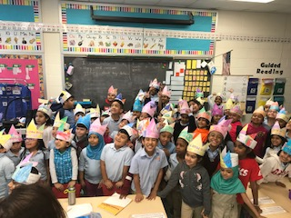 Classroom of children with paper crowns pose for picture for world read aloud day