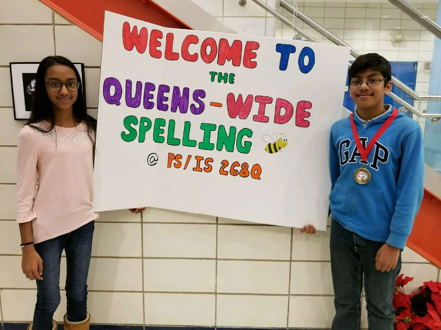 boy and girl finalist for spelling bee hold sign
