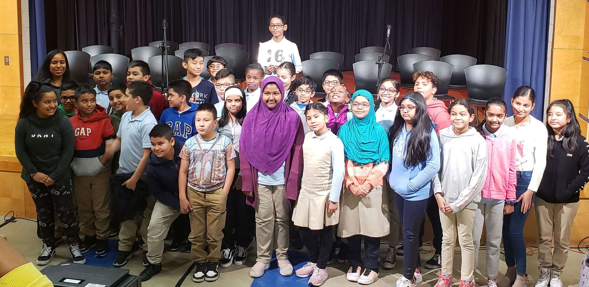 25 Students stand with one child winner of spelling bee