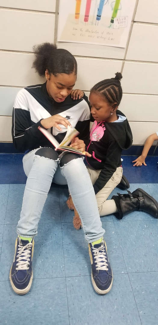 Older girl reads to a younger student on World read aloud day
