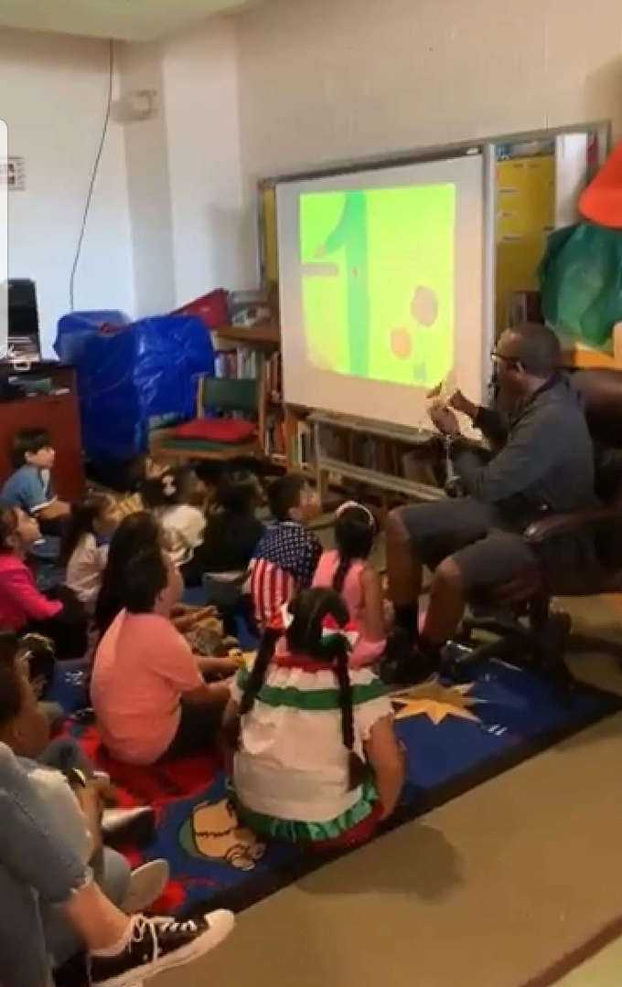 Author Mr Daniel Stewart reads books to younger students