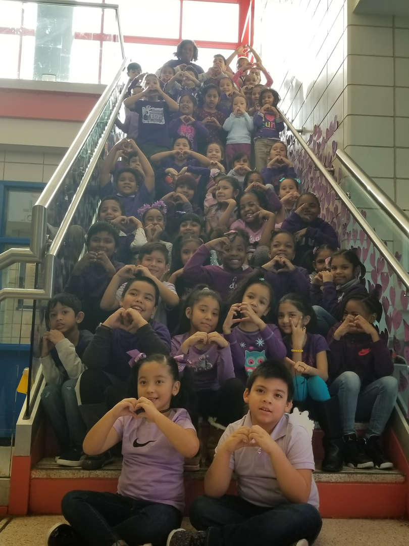 students pose on staircase for ps i love you day in a sea of purple