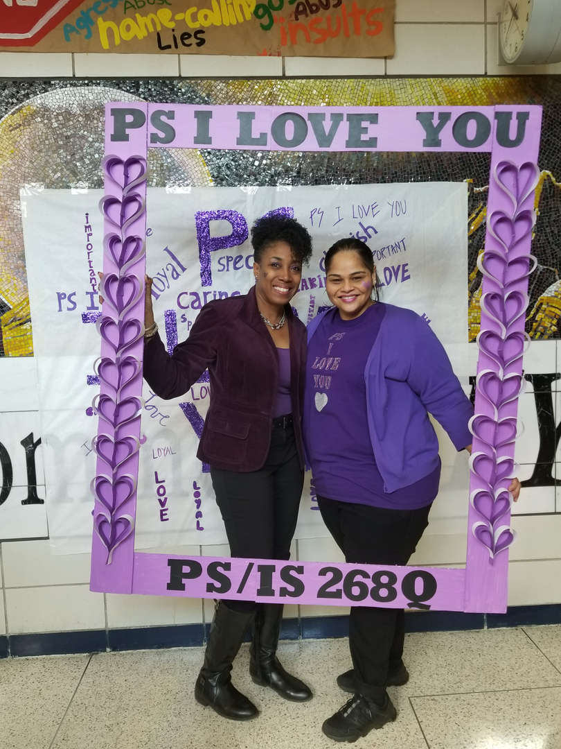staff members pose dressed in purple for ps i love you day