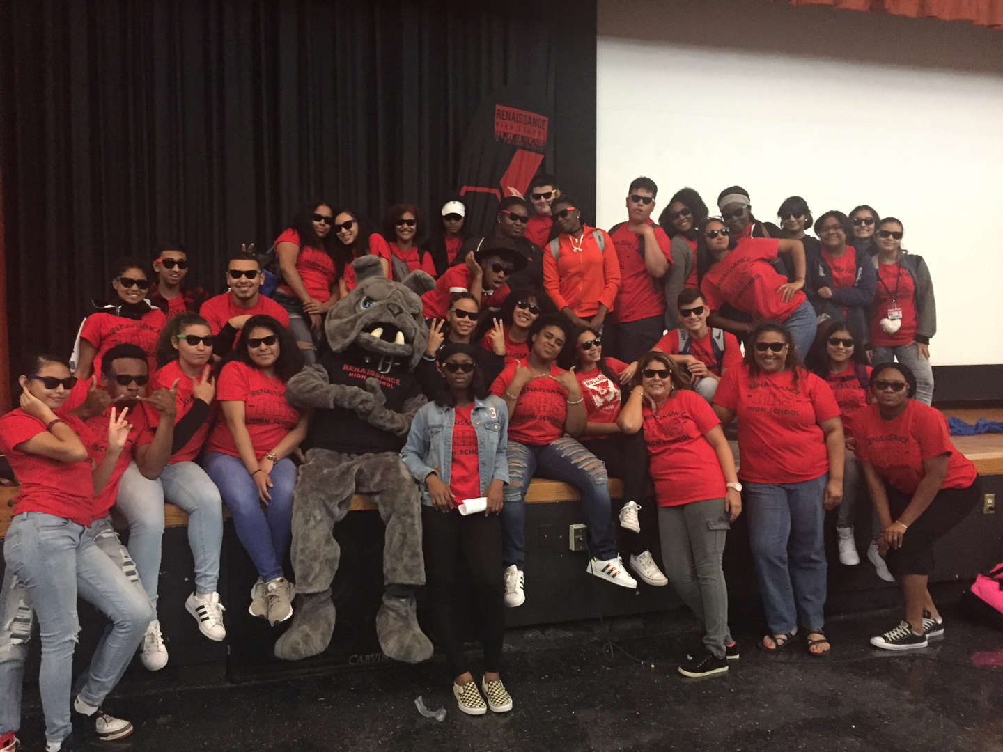 Large group of students wearing sunglasses with Bulldog Mascot