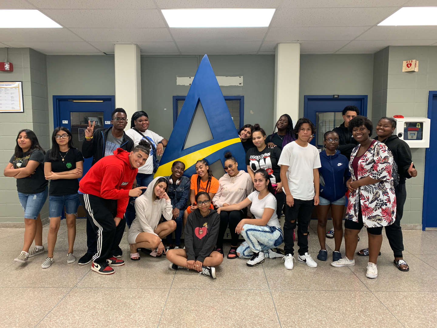 Group of Students in front of college logo on college tour