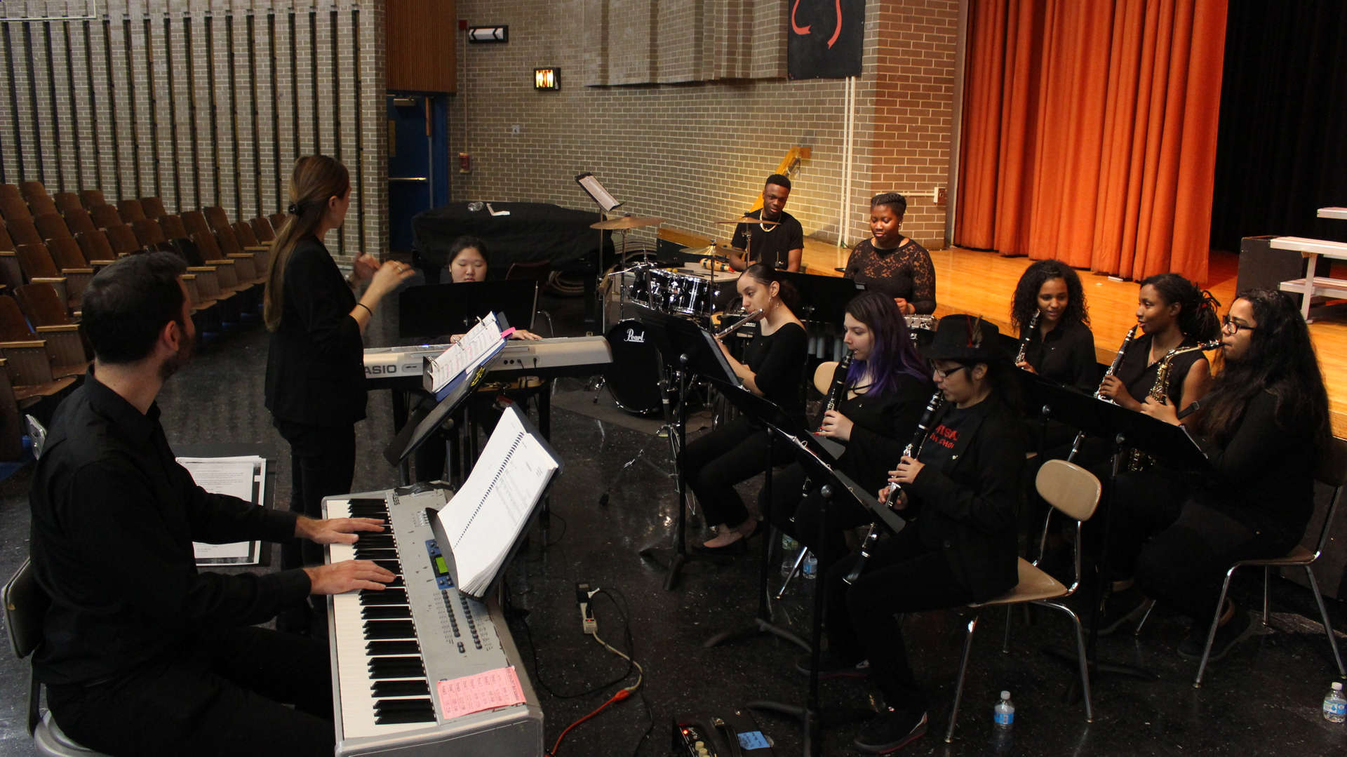 Students Playing Instruments with Teacher Conducting
