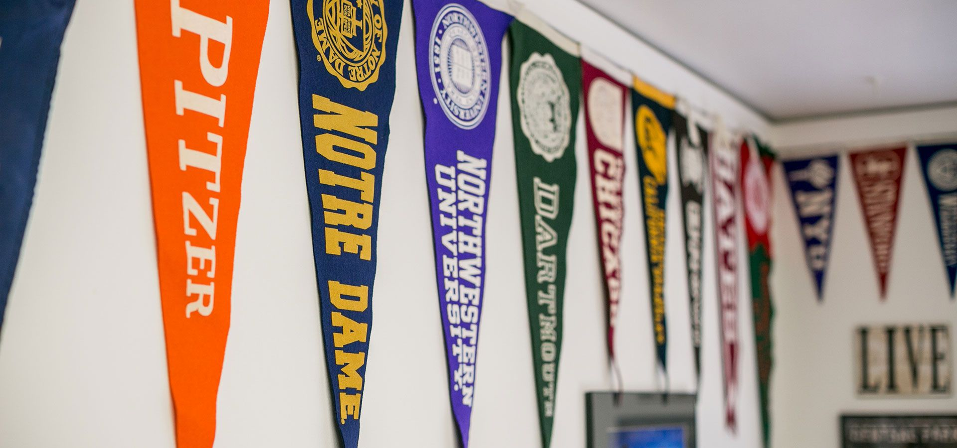 College pennants hanging on a wall