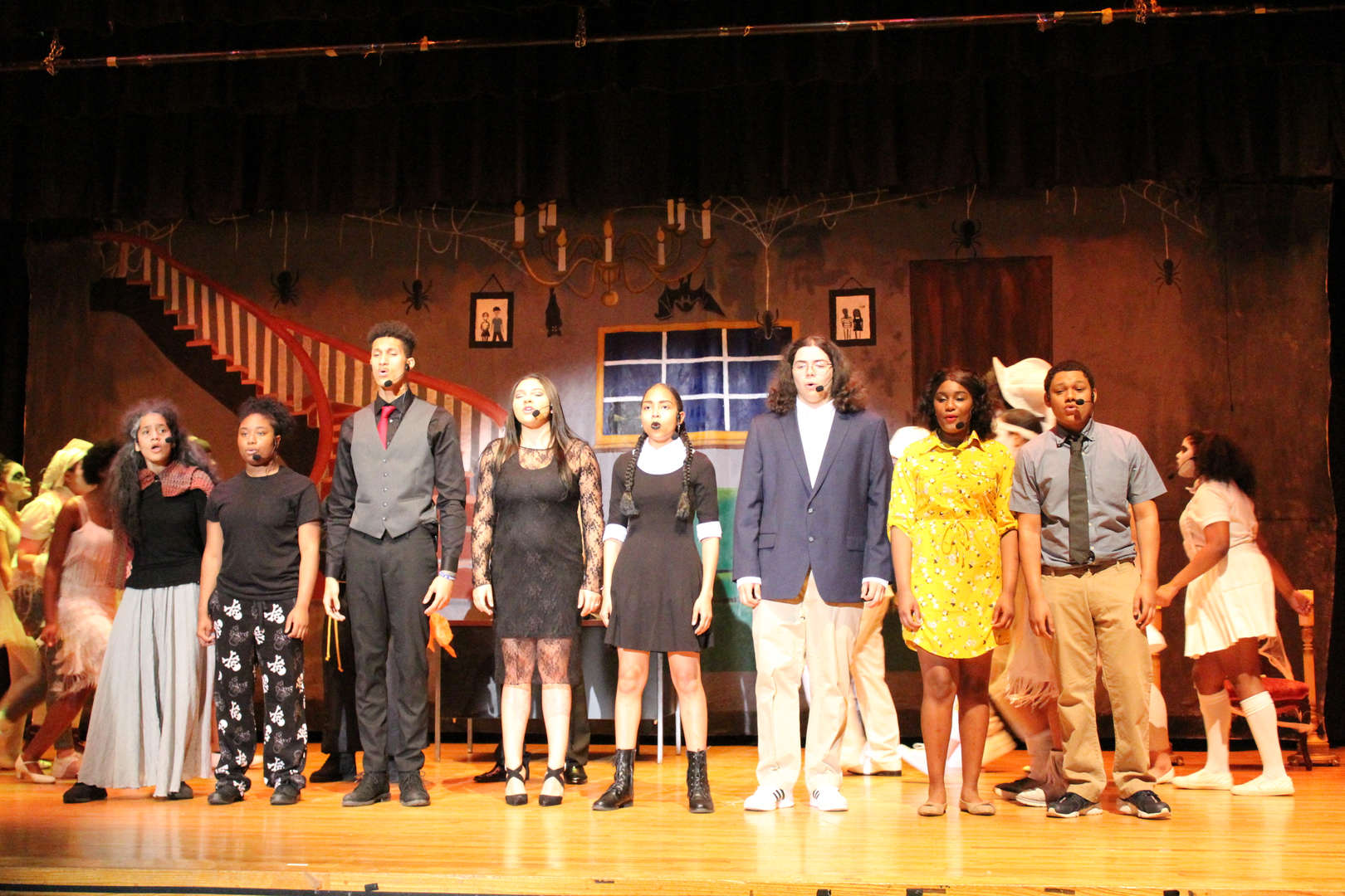 Eight students singing on stage during performance of The Addams Family