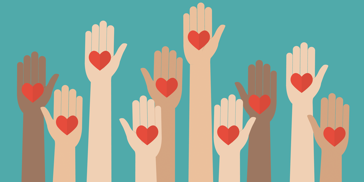 Raised hands of different skin colors with a heart in the palm of each hand
