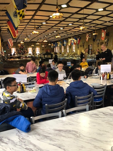 Students eating lunch with college students at the US Merchant Marine Academy.