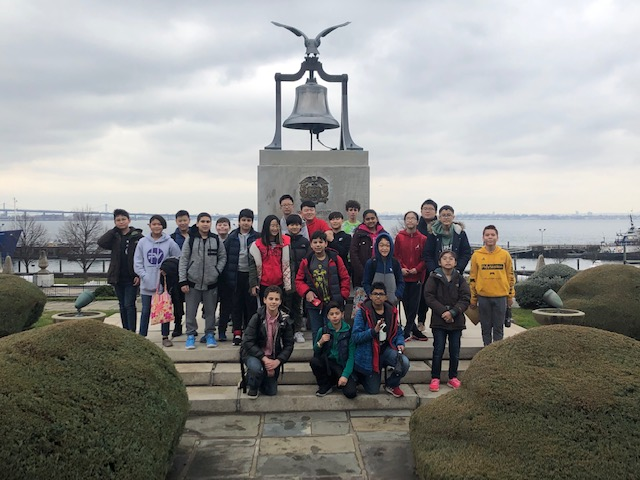 Students standing in front a memorial at the US Merchant Marine Academy.