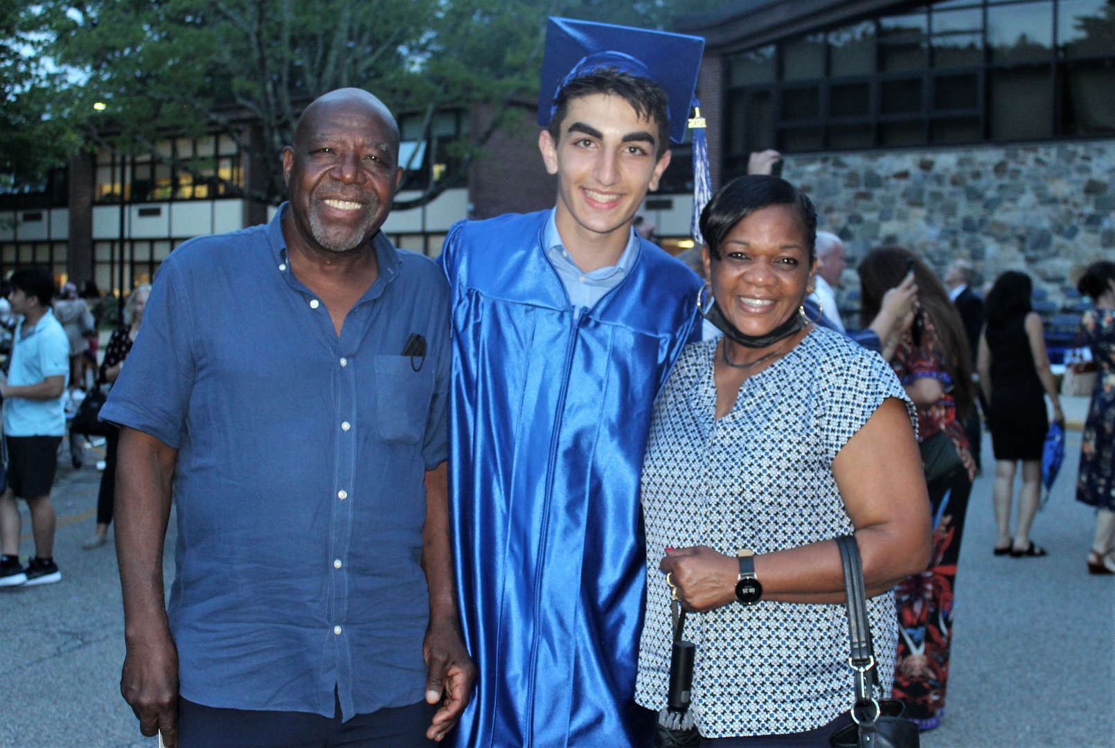 Graduate Zachary M. poses with school bus drivers.