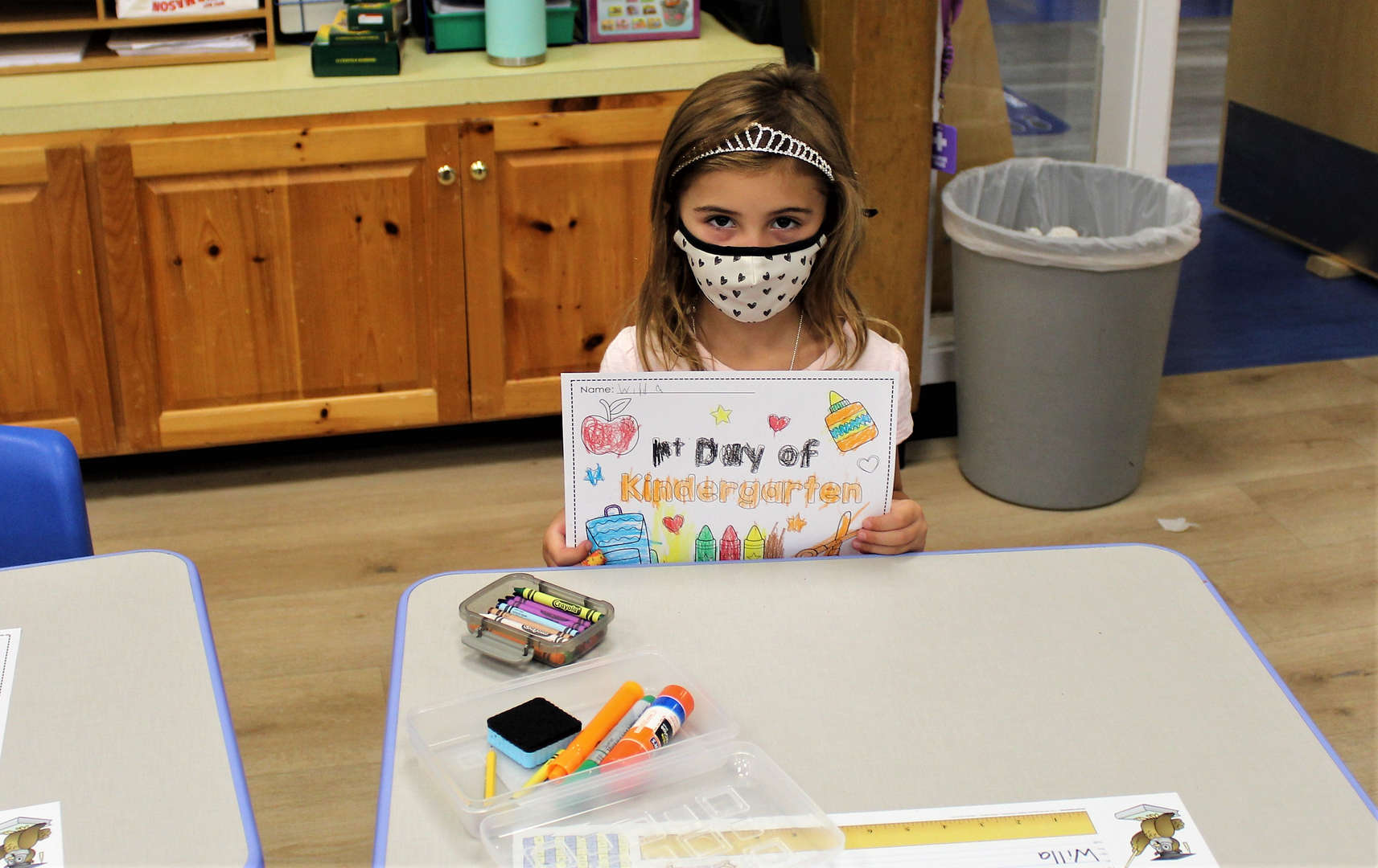 """A student holds up a """"first day of kindergarten"""" sheet that she colored in."""