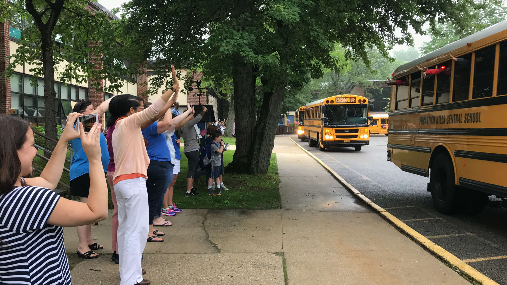 Staff members wave goodbye to school buses on the last day of school.