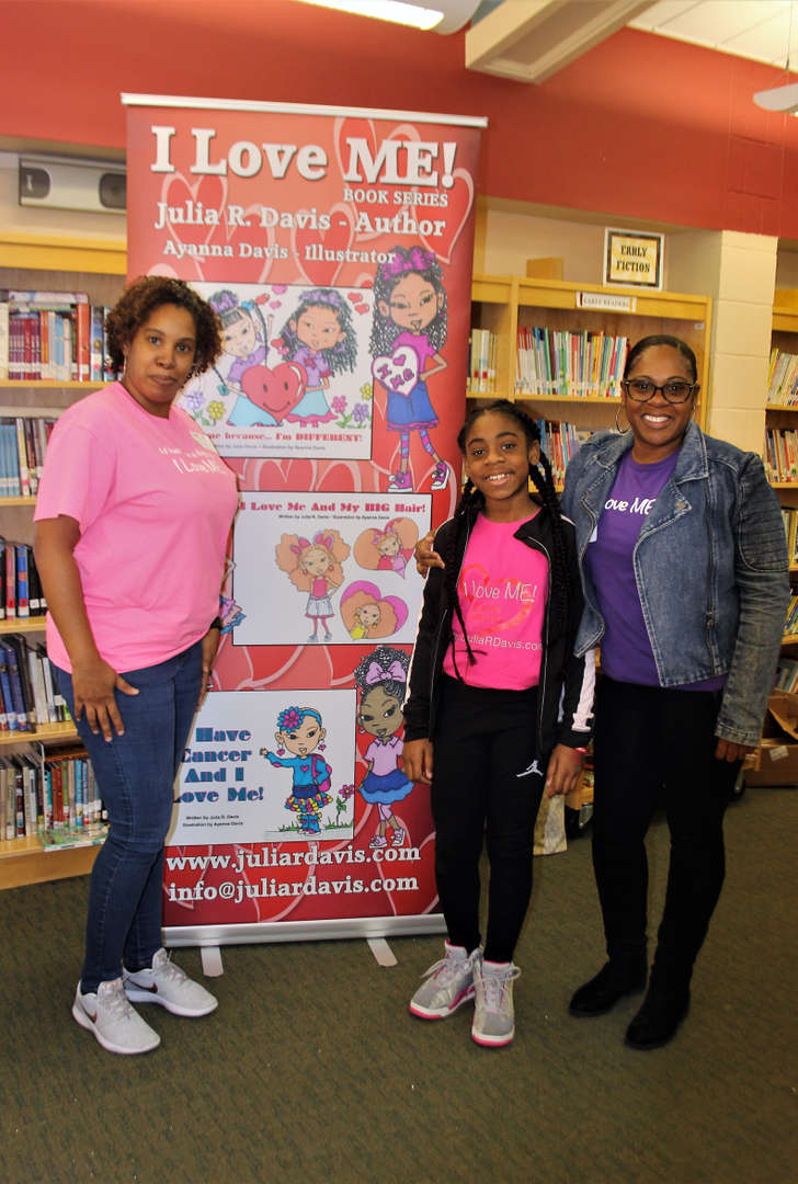 Author Julia Davis poses with her niece, Ty'Asia Carver, and sister, June Carver.