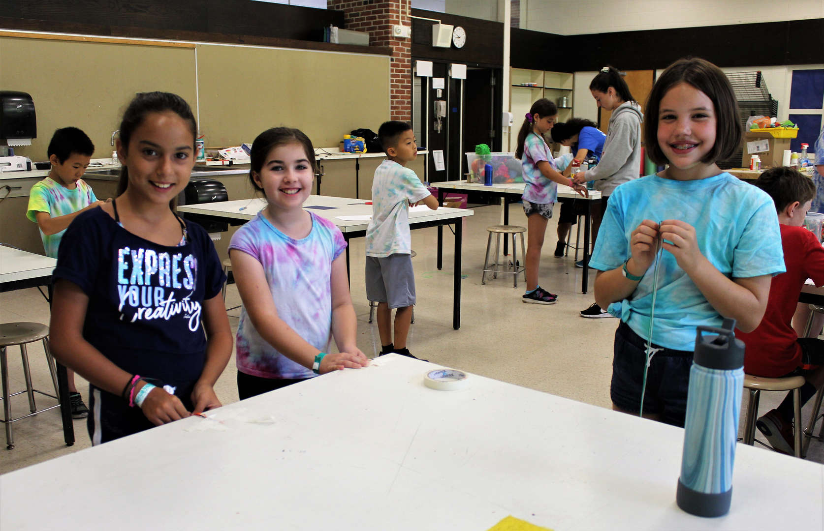 Girls making bracelets in arts and crafts.