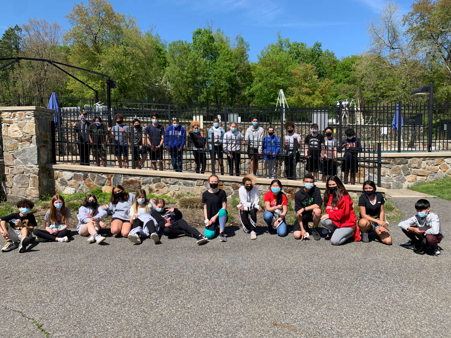 Eighth-grade students posing near the pool on campus.
