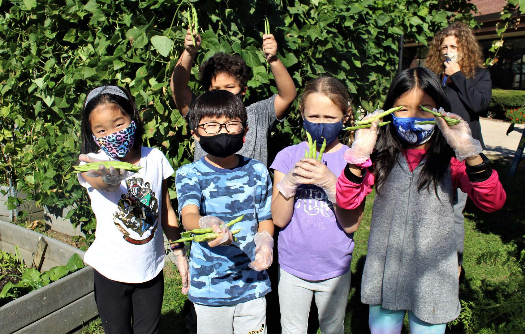 Five students show off the beans they harvested from the garden as their teacher looks on.