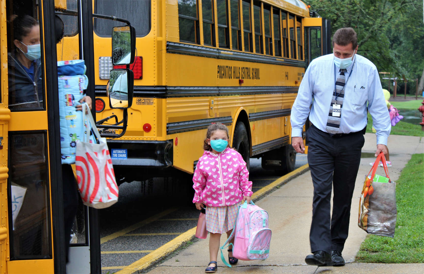Facilities Director Donald Booth helps a young girl off the school bus.
