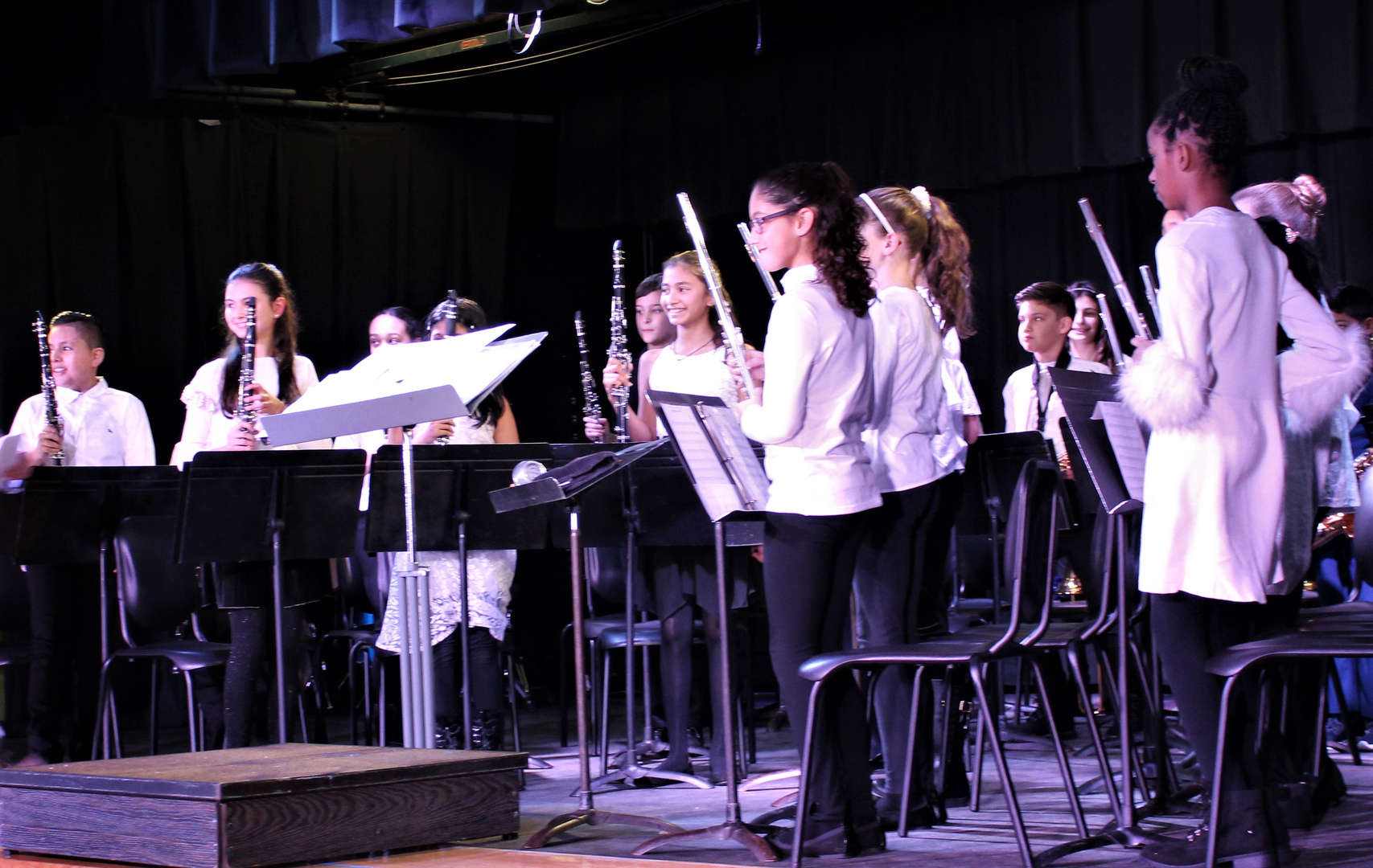 Members of the Fifth Grade Band stand as the audience claps for their performance in the Winter Concert.