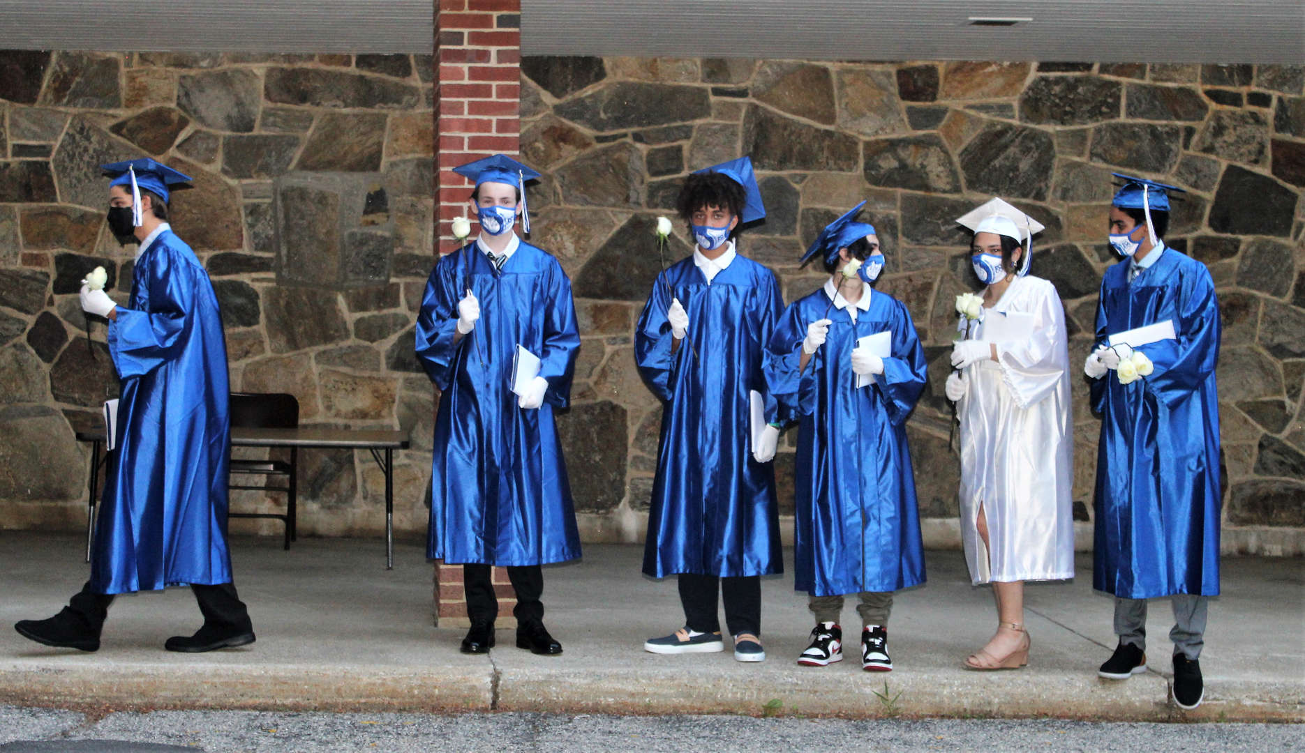 Graduates holding white roses to place beneath a plaque.