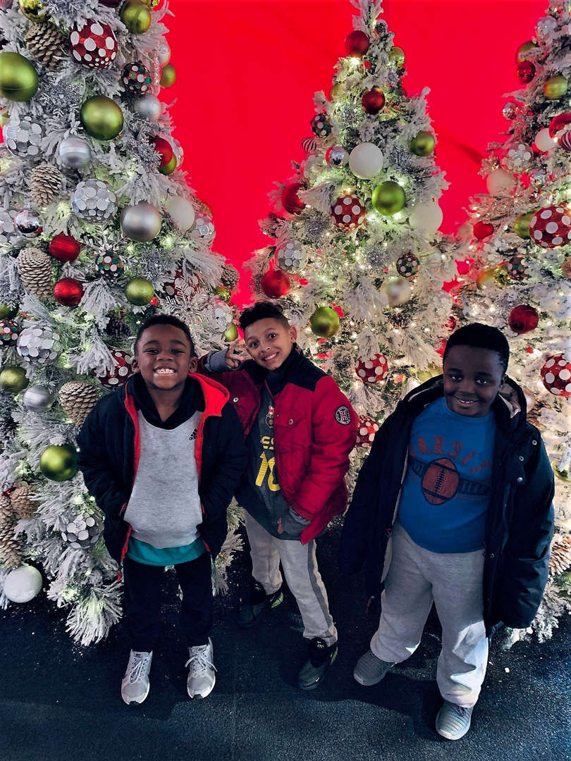 Children pose in front of silver Christmas trees.