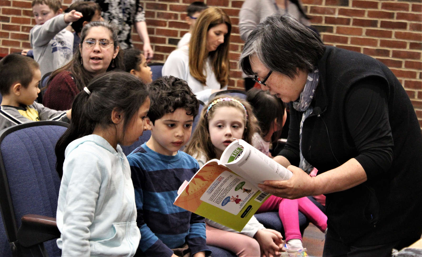 Author Janet Wong reads to several Pocantico students.