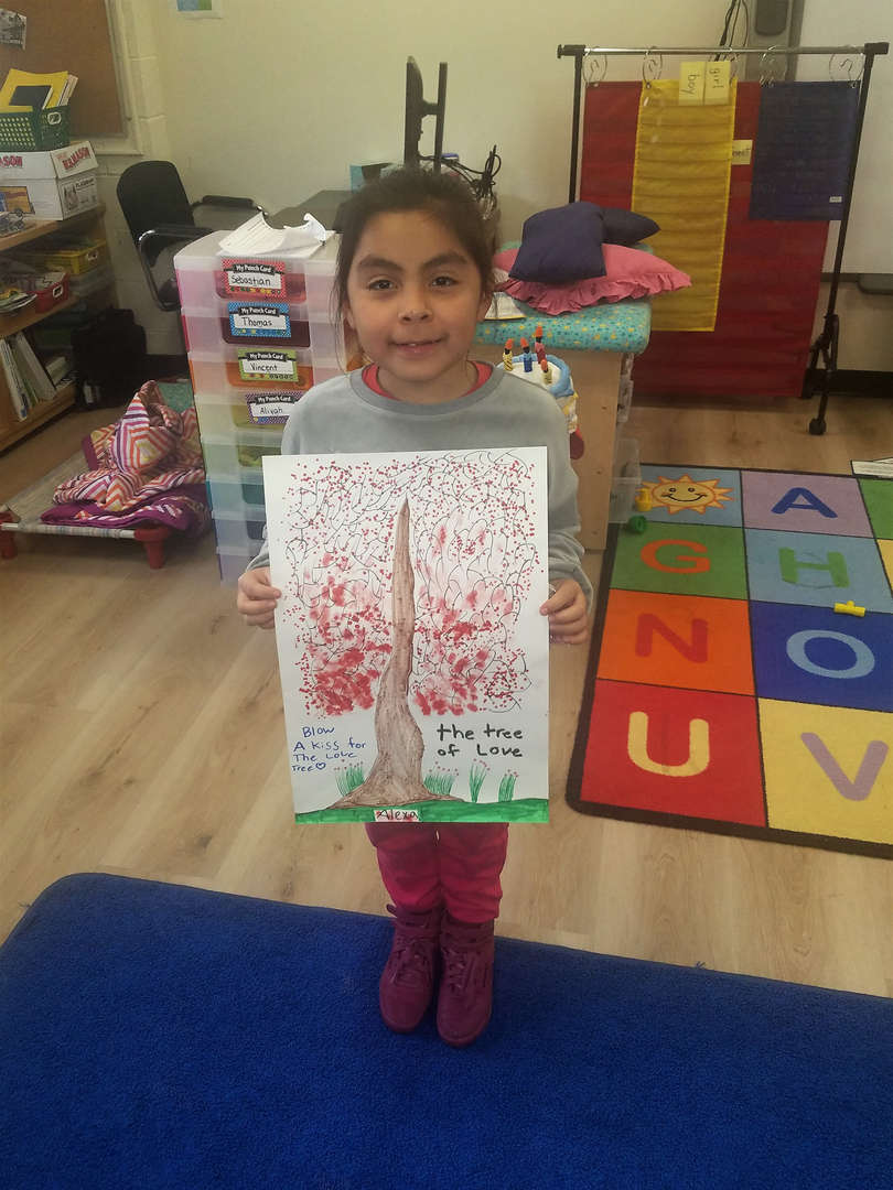 A student holds up artwork she created for a sick hospital patient.