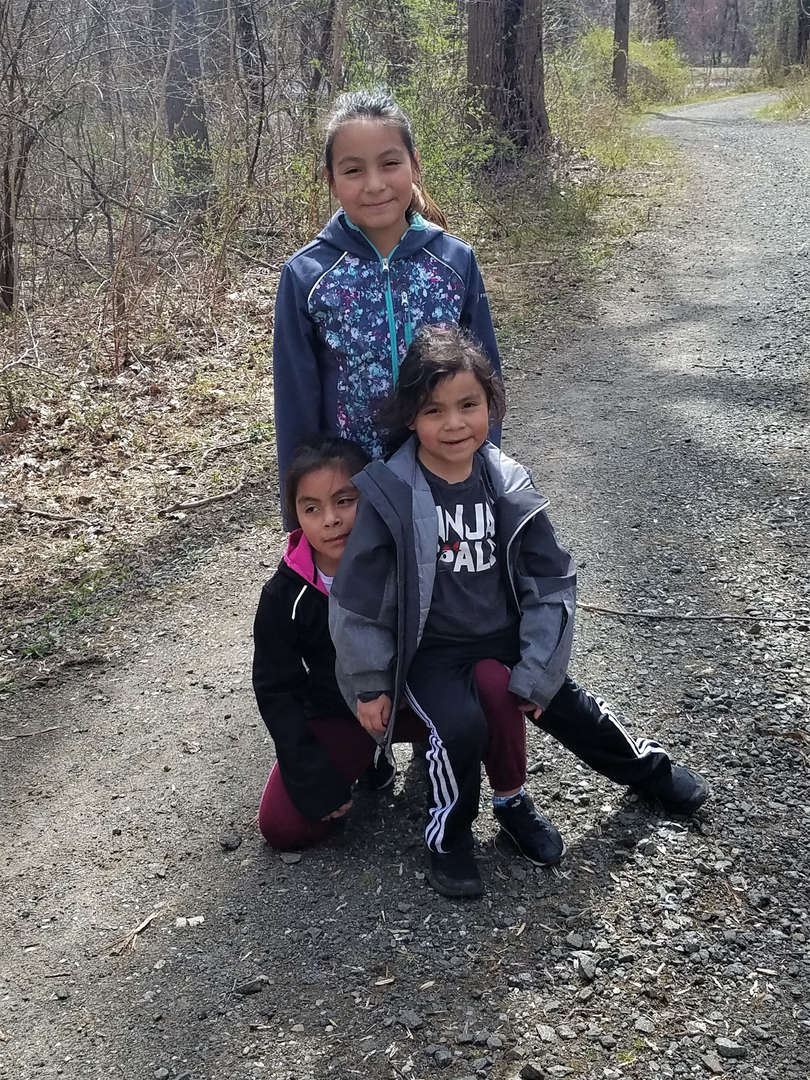 Three siblings stand together on a path near school.