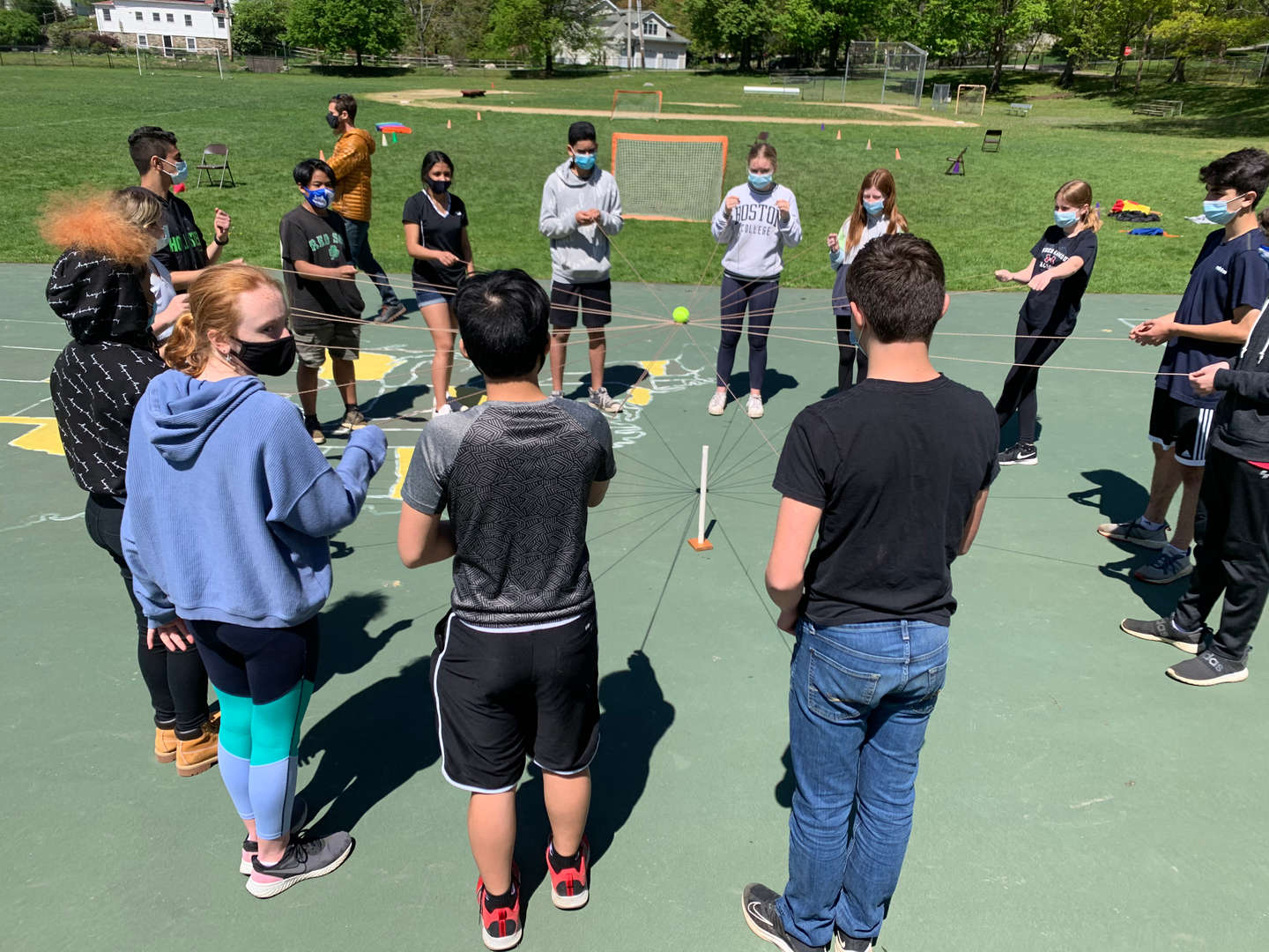 Students attempt to place a tennis ball balanced on strings on a mark.