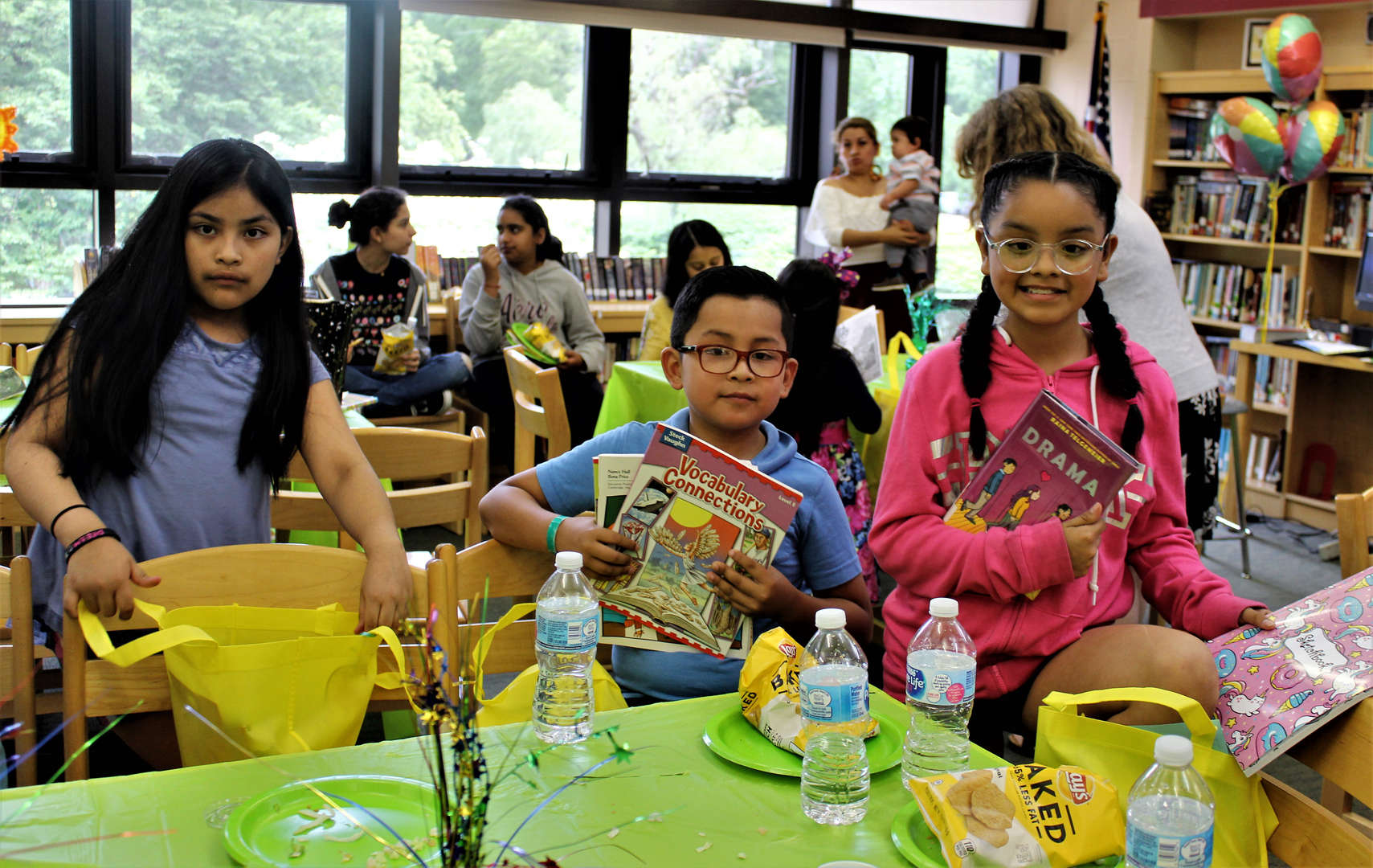 Students show off books and other gifts they received at the luncheon.