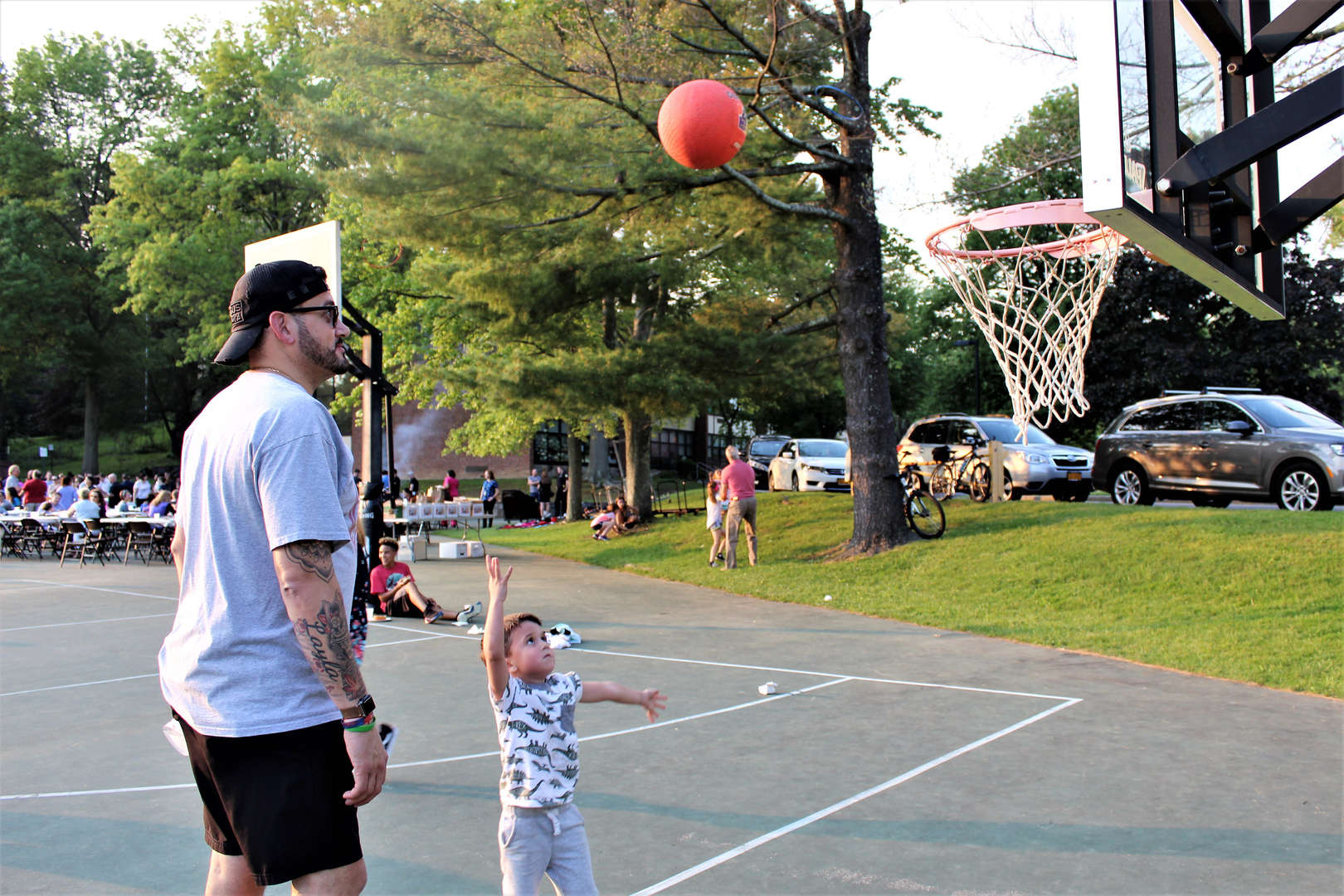A father and son play basketball.
