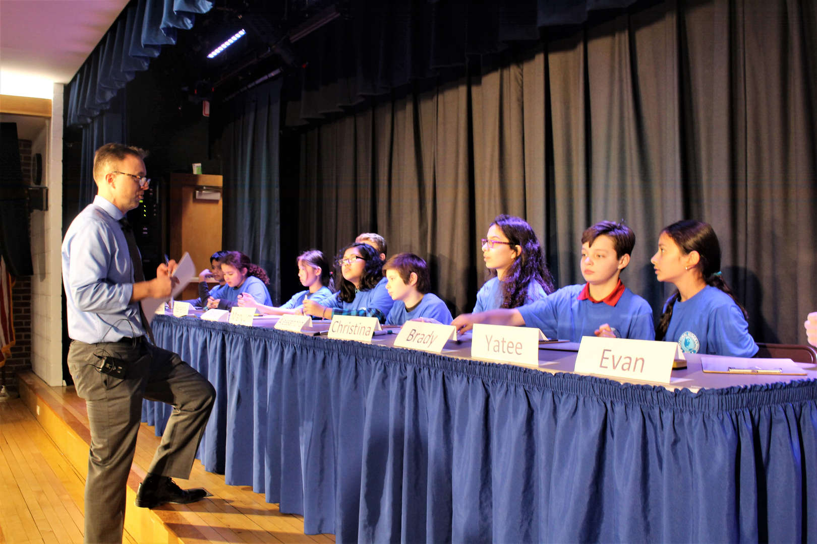 GeoBee moderator Adam Brown speaks with contestants.