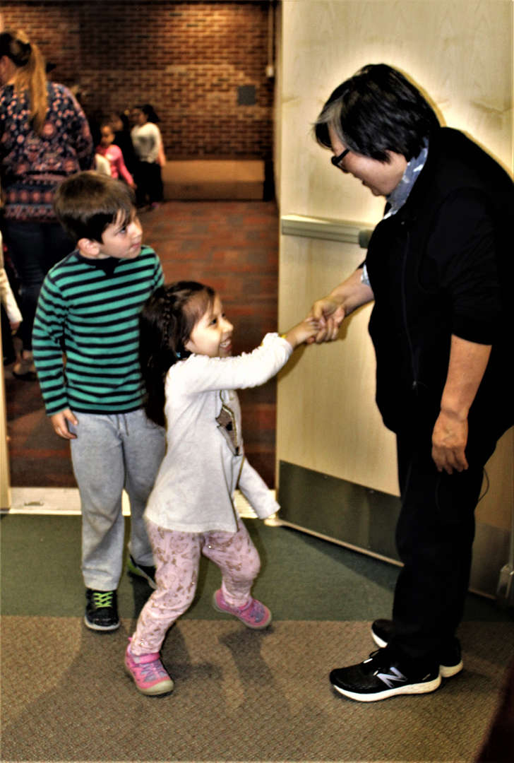 A child shakes Janet Wong's hand.