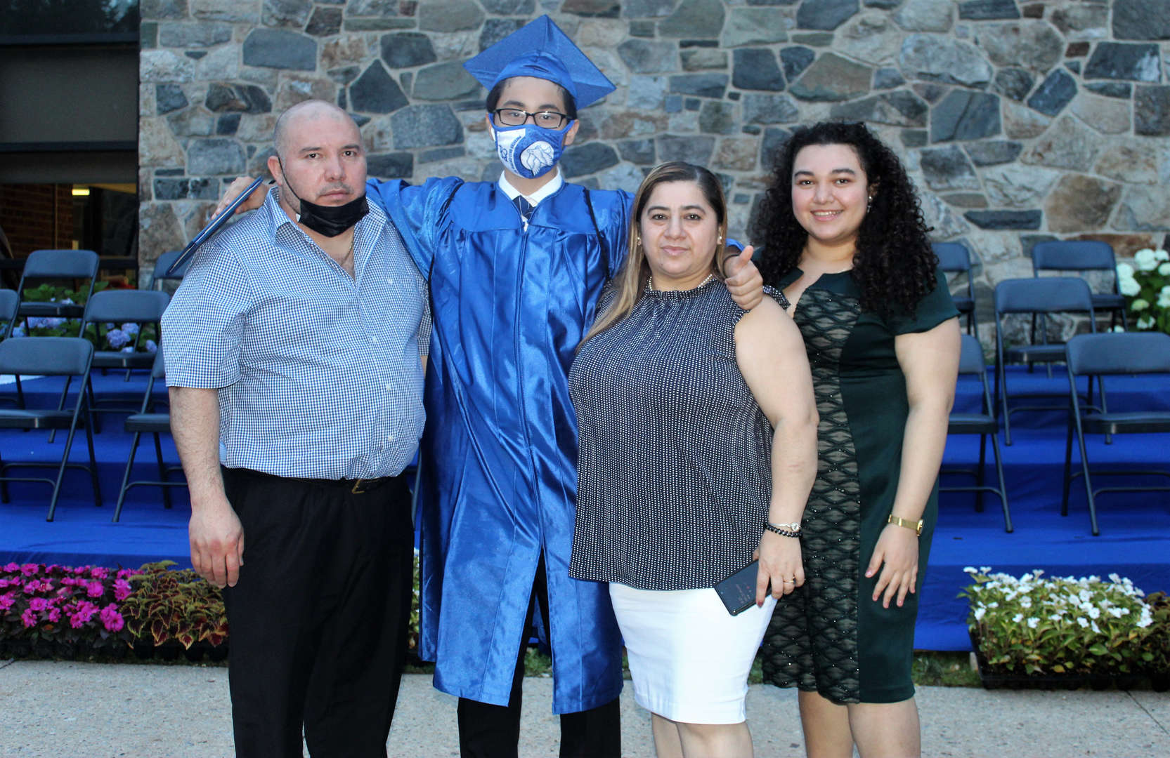 Eighth-grade boy poses with family after the ceremony.