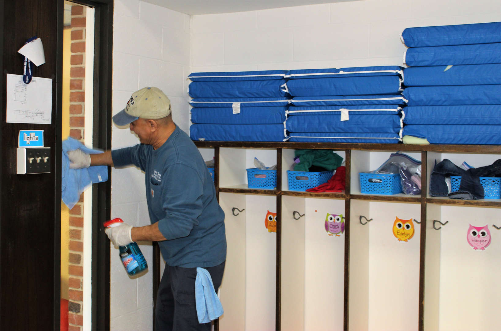 A member of the school's custodial staff helps clean a classroom.