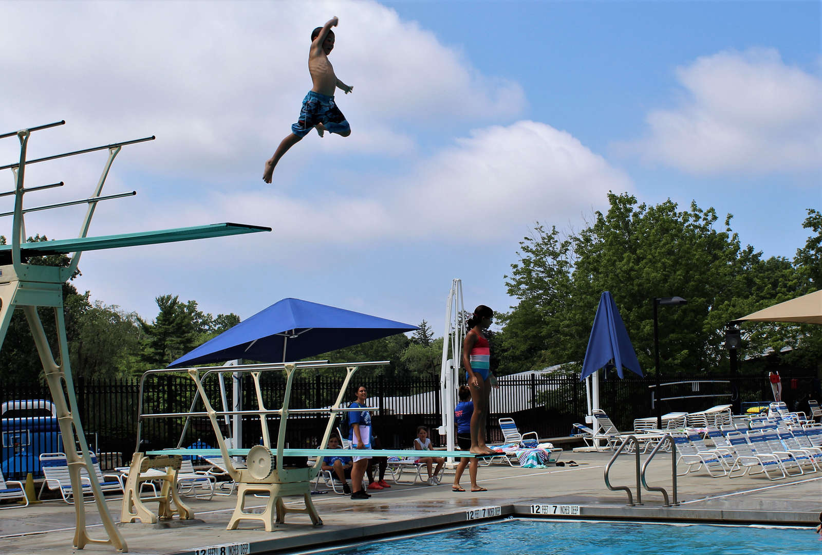 A boy takes a jump off the high dive board.