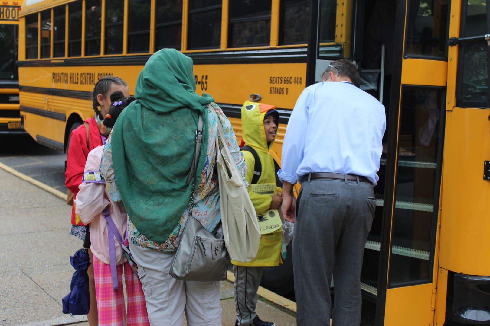 A staff member says goodbye to a student for the summer as the child boards his bus.