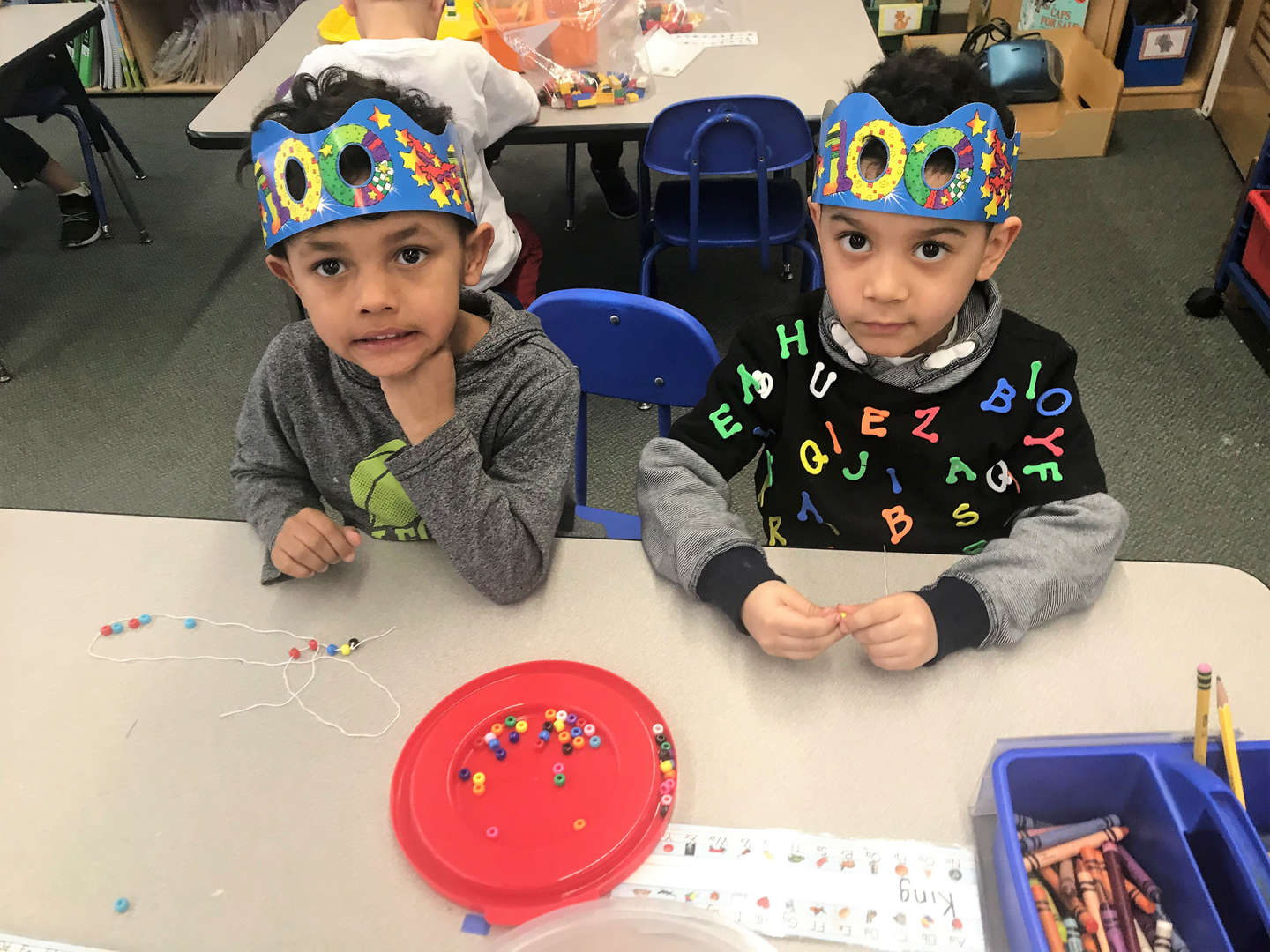 Two students put beads on strings during the 100 day celebration.