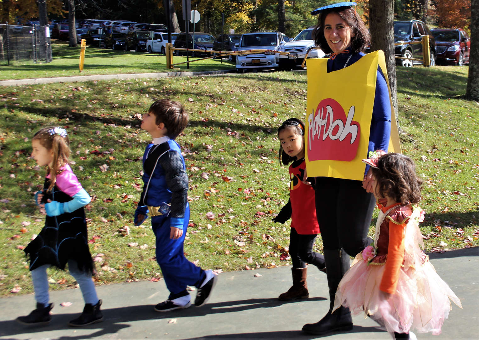 A teacher dressed as a Play-Doh container walks with students.
