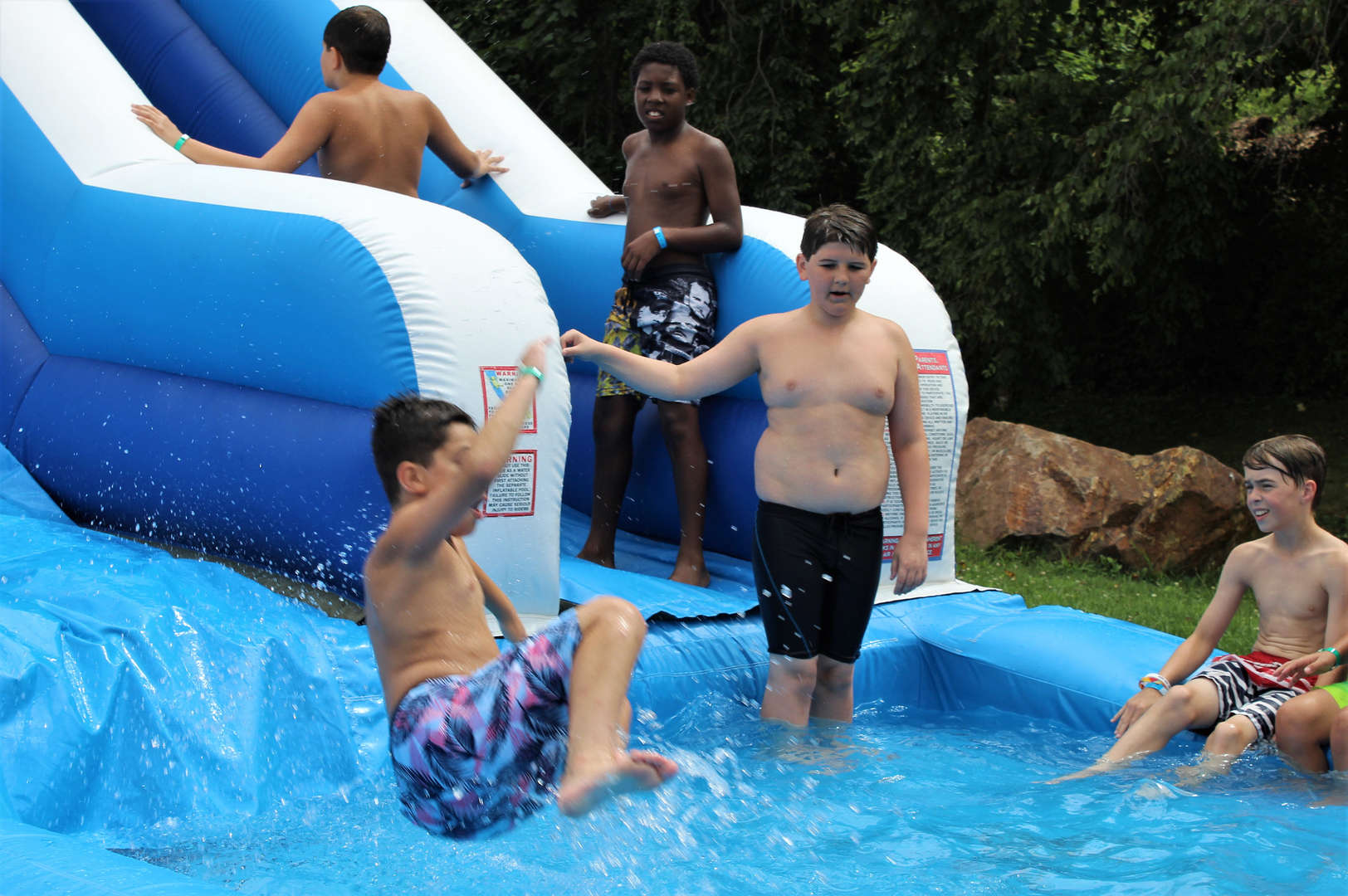 Students enjoying the inflatable water slide.