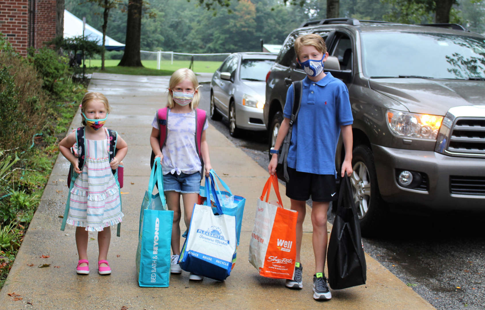 Three siblings walk into school after being dropped off.
